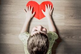 Ein kleiner Junge legt die Hände auf ein rotes Herz aus Papier.