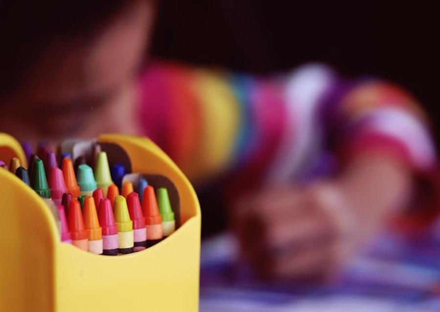 Wachsmaler in vielen Farben, unscharf ein Kind beim Malen - Vielfalt in Aktion.