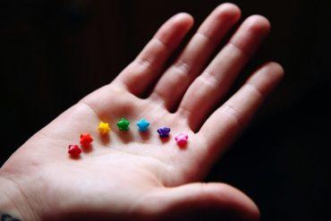 Sexuelle Vielfalt: Hand präsentiert 7 Zuckersternchen in Regenbogenfarben